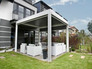 White Selt System Sunbreaker 400 Pergola, side view, lawn with patio and pergola installed above outdoor furniture setting, slats in closed position