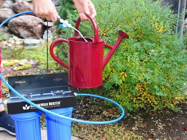 GrowMax Water Eco Grow 240 in a garden with someone filling a red watering can from it