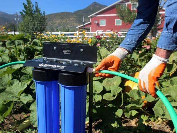 GrowMax Water Pro Grow 2000 installed in garden with gardener holding a hose