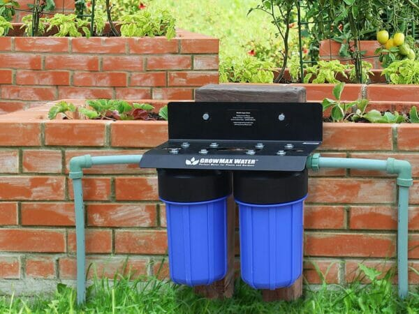 GrowMax Super Grow 800 installed in front of brick raised garden bed