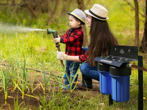 GrowMax Super Grow 800 installed in garden where a mother with her child are watering directly from the unit